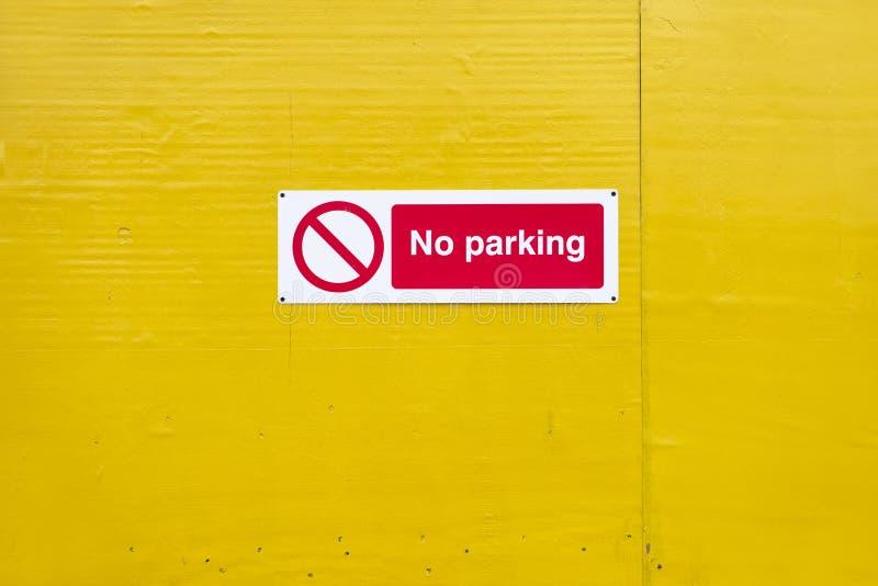 Inget parkera tecken på den gula tomma väggen royaltyfri foto