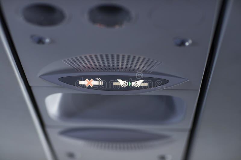 Inget - röka och fäst säkerhetsbältet undertecknar i flygplanet arkivfoto