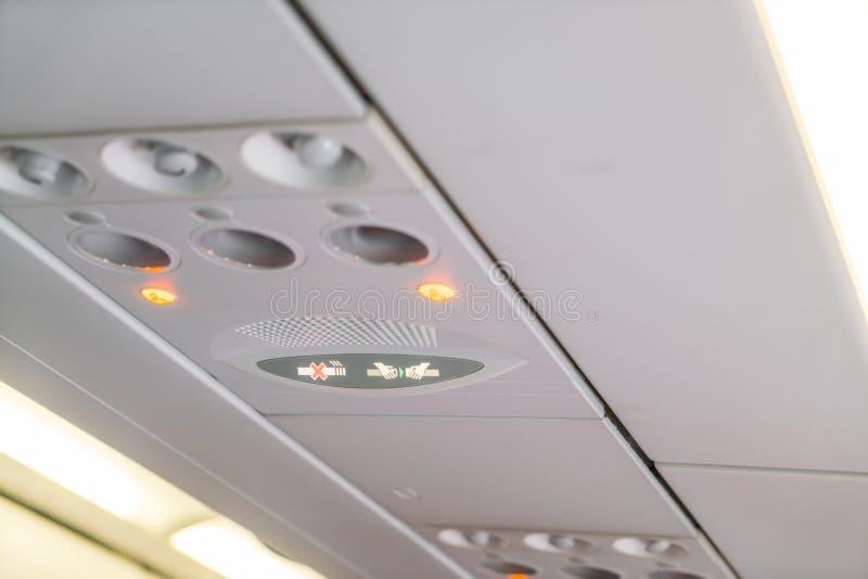 Inget - röka tecknet och säkerhetsbältet underteckna på flygplanet royaltyfri foto