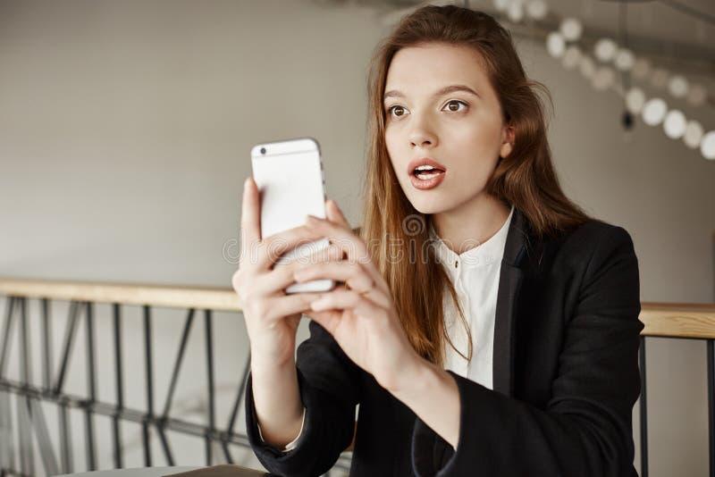 Inget ska tro mig som jag såg den Inomhus skott av häpet och förvånat kvinnasammanträde i kafét, hållande smartphone medan arkivbilder