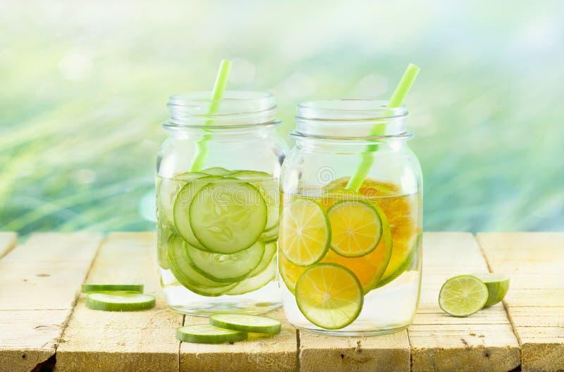 Ingett detoxvatten, tappning och pastellfärgad färg tonar, bantar detoxen citronen och gurkan på tränaturbakgrund royaltyfri fotografi