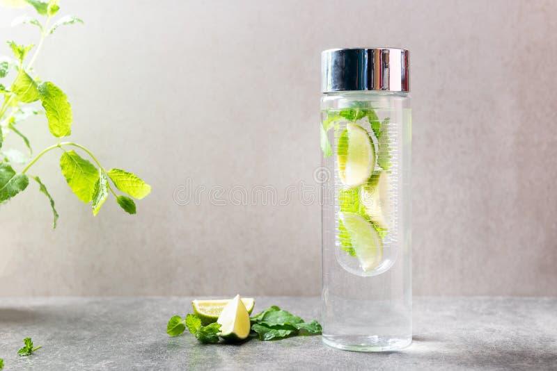Ingett vatten med limefrukt och mintkaramellen i special flaska arkivfoto