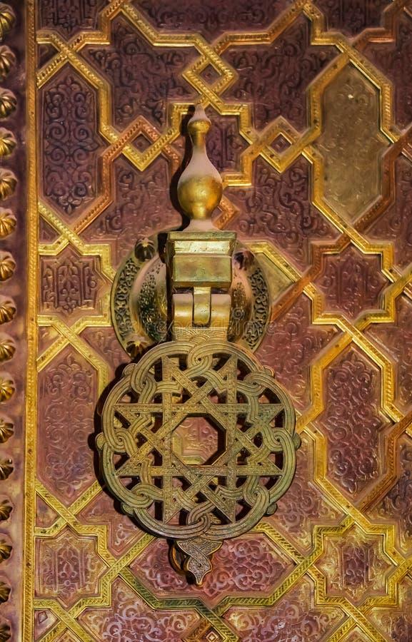 Ingewikkelde overladen metaalkloppers op een poort in Fes Marokko stock afbeelding