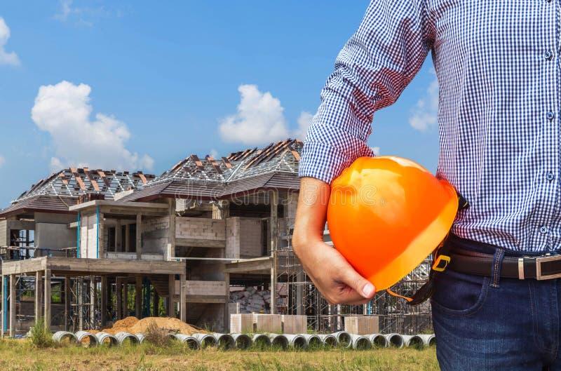 Ingezetene ingenieur die gele veiligheidshelm houden bij de nieuwe huisbouw stock afbeelding