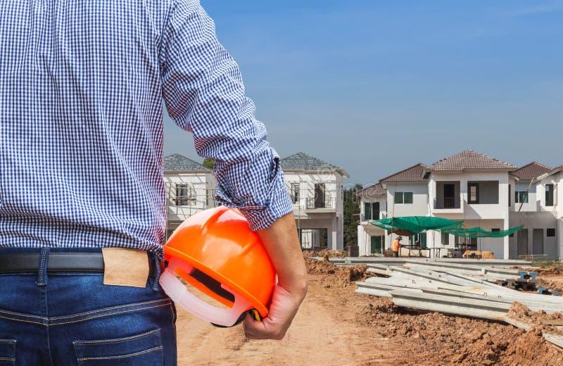 Ingezetene ingenieur die gele veiligheidshelm houden bij nieuw huis die in aanbouw plaats bouwen stock fotografie