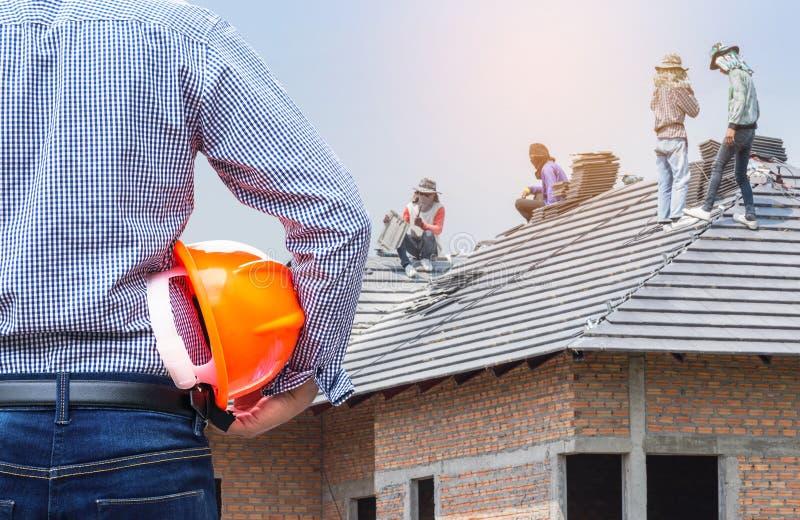Ingezetene ingenieur die gele veiligheidshelm houden bij nieuw huis die in aanbouw plaats met arbeiders bouwen die betontegel ins stock afbeeldingen