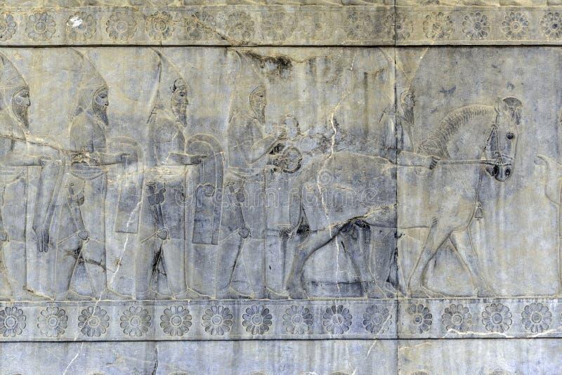 Ingezetenen van historisch imperium met dieren Steen bas-hulp in oude stad Persepolis, Iran stock foto's