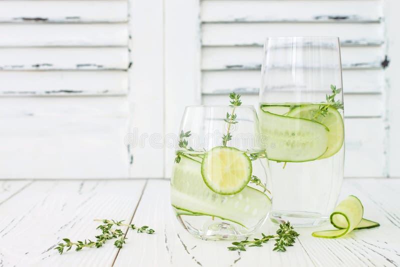 Ingiven gurka hydratisera vatten med timjan och limefrukt Hemlagad smaksatt lemonad på den lantliga gamla trätabellen arkivbild