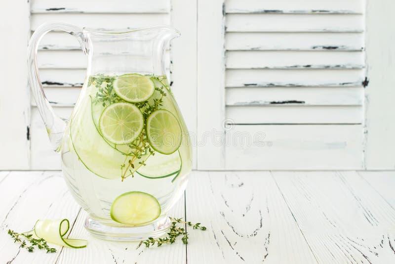 Ingiven gurka hydratisera vatten med timjan och limefrukt Hemlagad smaksatt lemonad på den lantliga gamla trätabellen arkivfoton