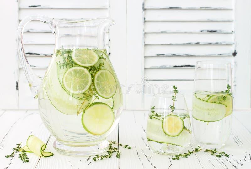 Ingiven gurka hydratisera vatten med timjan och limefrukt Hemlagad smaksatt lemonad på den lantliga gamla trätabellen arkivfoto