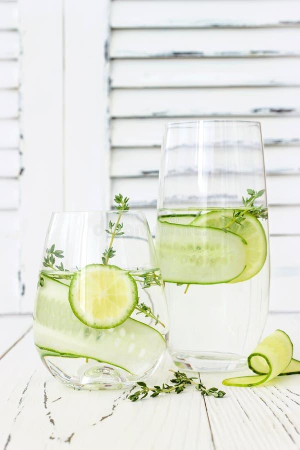 Ingiven gurka hydratisera vatten med timjan och limefrukt Hemlagad smaksatt lemonad på den lantliga gamla trätabellen royaltyfri bild
