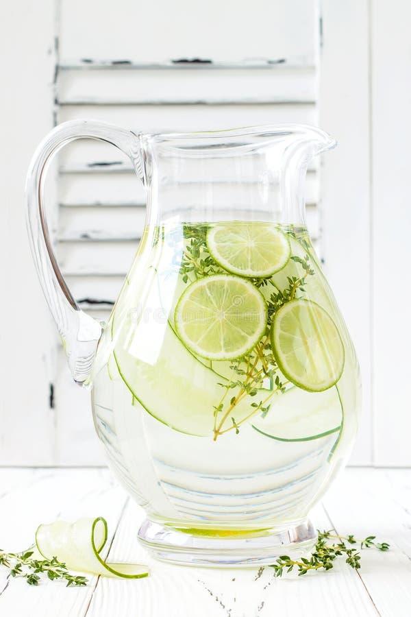 Ingiven gurka hydratisera vatten med timjan och limefrukt Hemlagad smaksatt lemonad på den lantliga gamla trätabellen royaltyfri foto
