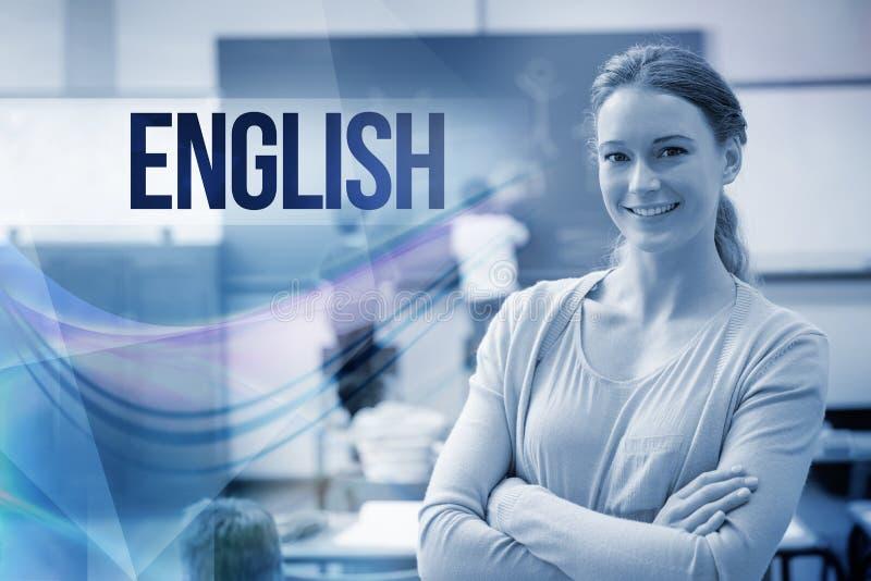 Inglés contra el profesor bonito que sonríe en la cámara en la parte posterior de la sala de clase fotografía de archivo libre de regalías