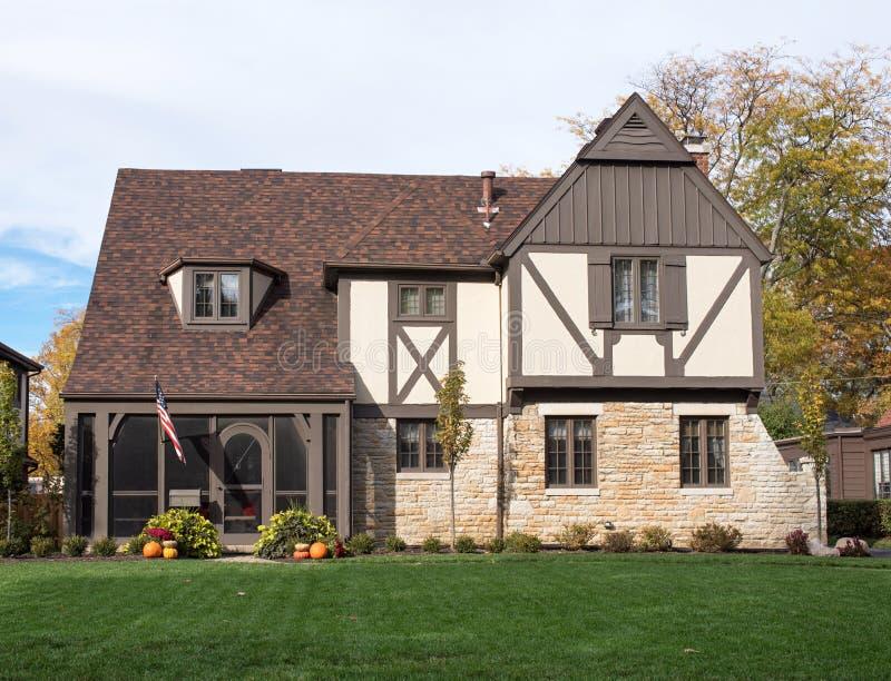 Inglés Tudor Home con la bandera americana y las calabazas imagen de archivo