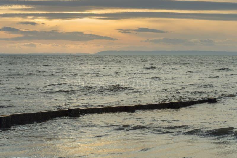 Ingle de madera de la playa semi sumergida por marea en la puesta del sol Cuesta británica fotografía de archivo libre de regalías