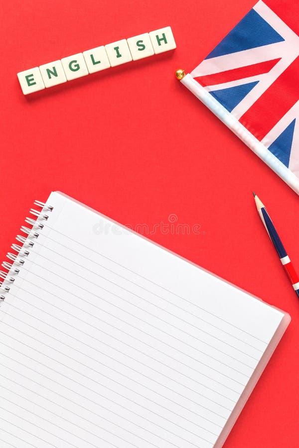 Inglese di parola una matita con il blocco note governato su rosso fotografia stock libera da diritti