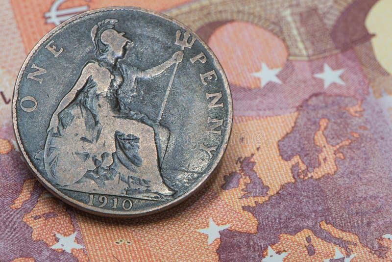 Ingleses velhos uma moeda da moeda de um centavo ajustaram-se em uma cédula do Euro dez fotografia de stock