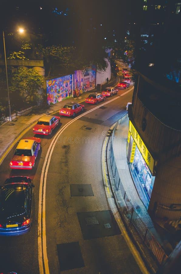 Ingorgo stradale in Hong Kong alla notte Automobili di Taxy che stanno nella coda Via della ripresa esterna della curva fotografia stock
