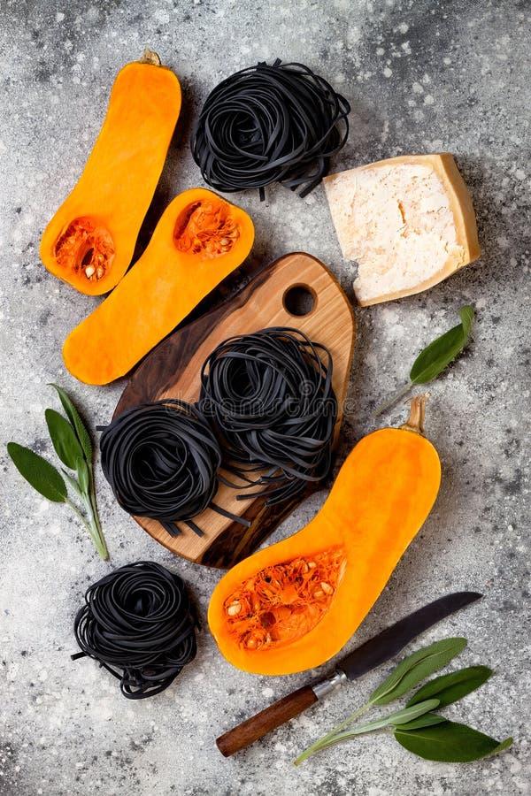 Ingrédients crus pour faire les pâtes noires avec la courge de butternut, le parmesan et la sauge Dîner noir et orange de Hallowe images stock