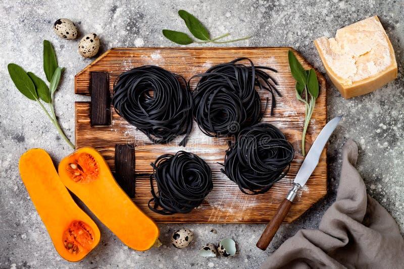 Ingrédients crus pour faire les pâtes noires avec la courge de butternut, le parmesan et la sauge Dîner noir et orange de Hallowe photo libre de droits