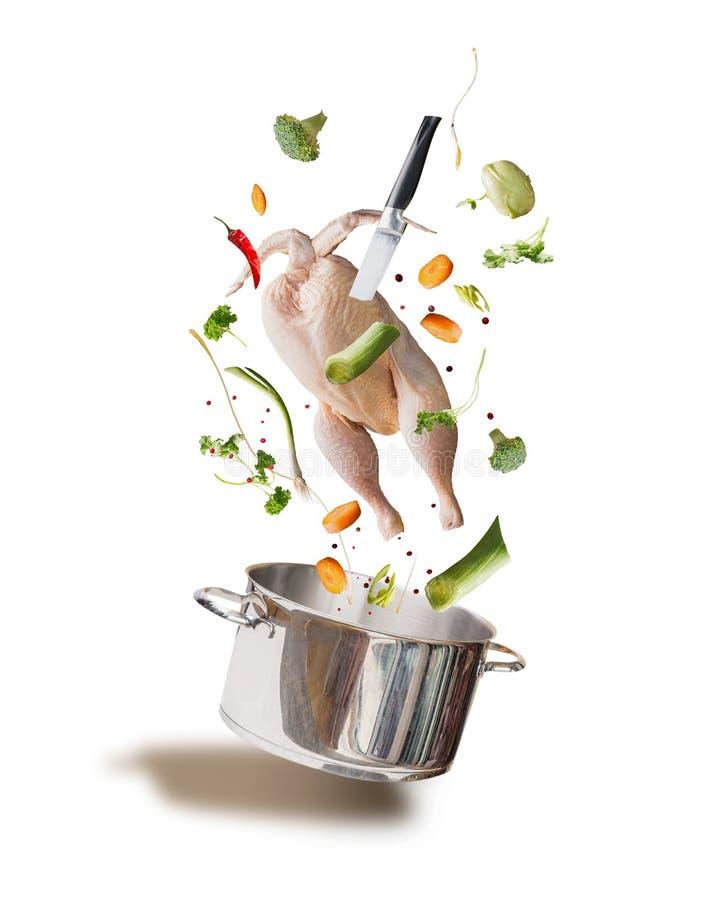 Ingrédients crus volants de bouillon de poulet, de bouillon ou de soupe avec le poulet entier, légumes, assaisonnement, couteau e image libre de droits