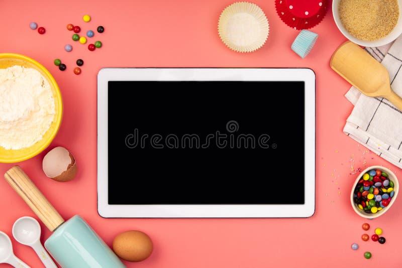 Ingrédients de cuisson avec le comprimé vide sur le fond rose, configuration plate images libres de droits