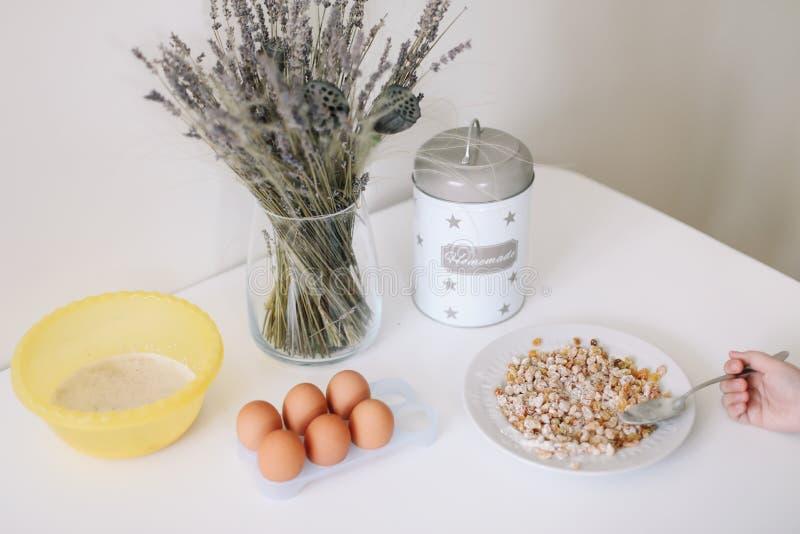 Ingrédients de cuisson pour la pâtisserie dans la cuisine Faisant cuire des ingrédients - oeufs, sucre, raisin sec, farine au-des photographie stock