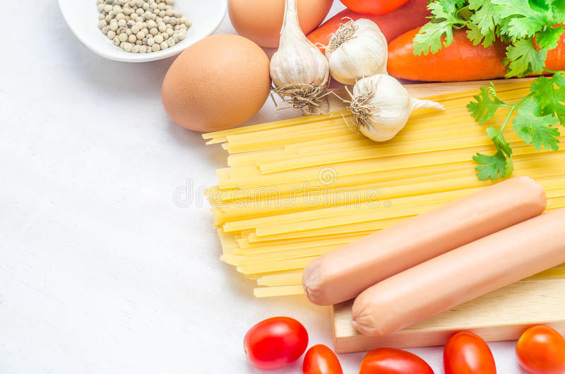 Ingrédients de pâtes avec les hot-dogs sur le fond en bois blanc dessus images stock