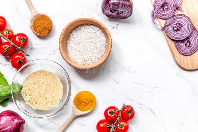 Ingrédients de Paella avec du riz, le sel, des épices et des tomates sur la moquerie blanche de vue supérieure de fond de table  photos libres de droits