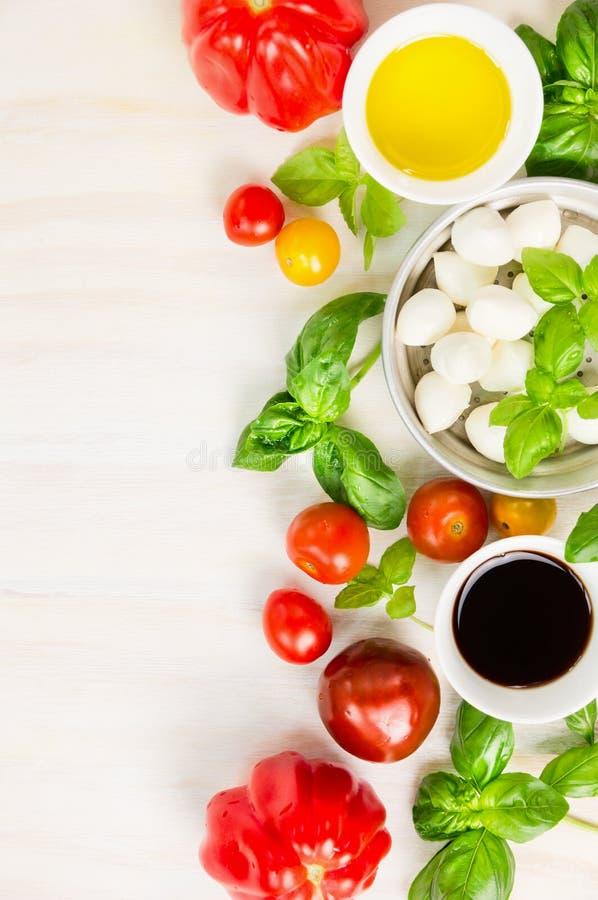 Ingrédients de salade de tomates de mozzarella sur le fond en bois blanc, vue supérieure image stock