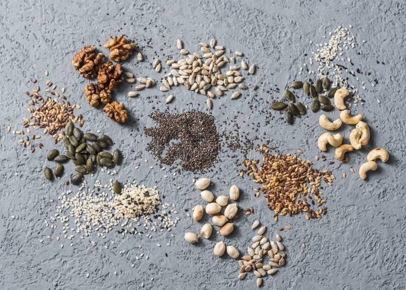 Ingrédients de Superfood Graines et écrous d'Assortiment sur un fond gris, vue supérieure Les graines de lin, les graines de sésa images libres de droits