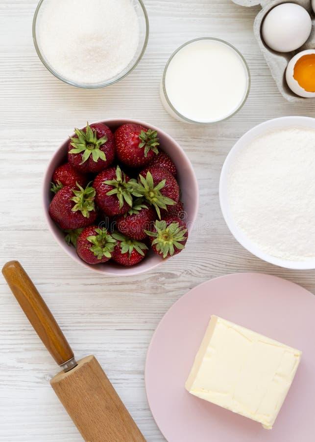 Ingrédients farine, oeufs, beurre, lait, sucre, fraise, vue de tarte de fraise d'en haut Cuisson du tarte ou du gâteau de fraise  photographie stock libre de droits
