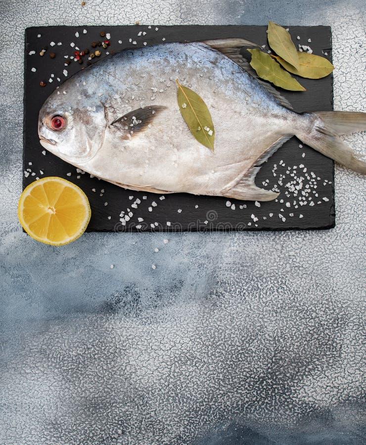 Ingrédients frais de pompano et d'épice de poisson cru sur la table photos libres de droits