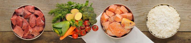 Ingrédients naturels pour des aliments pour chiens dans des quatre cuvettes sur vieil en bois photo libre de droits