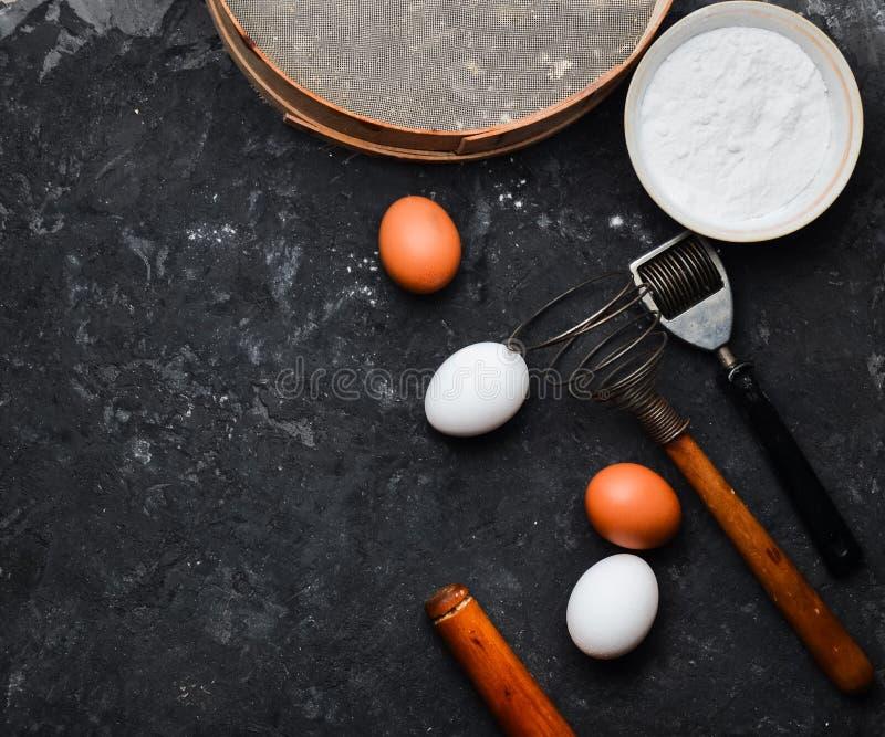 Ingrédients pour des pâtes Le procédé de cuisson Oeufs, farine, outils de cuisine sur une table concrète noire Outils pour la cui image libre de droits