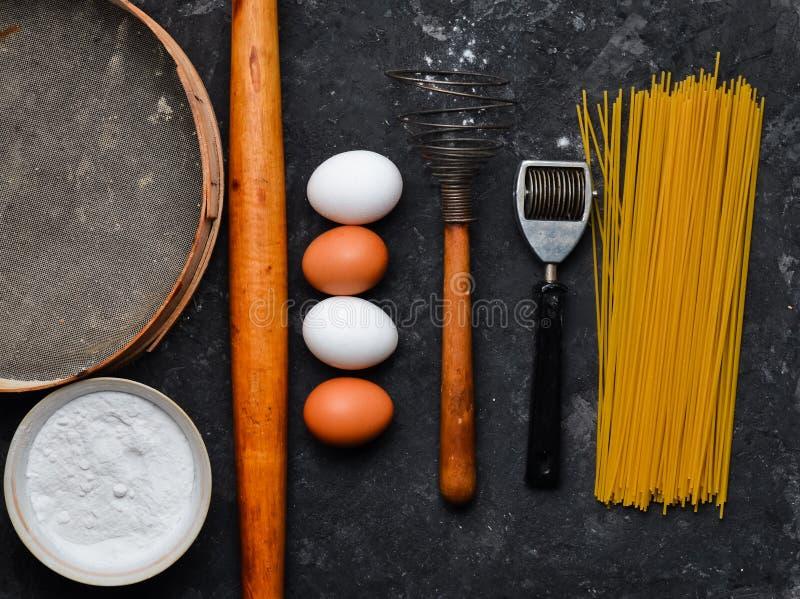 Ingrédients pour des pâtes Le procédé de cuisson Oeufs, farine, outils de cuisine sur une table concrète noire Outils pour la cui images libres de droits