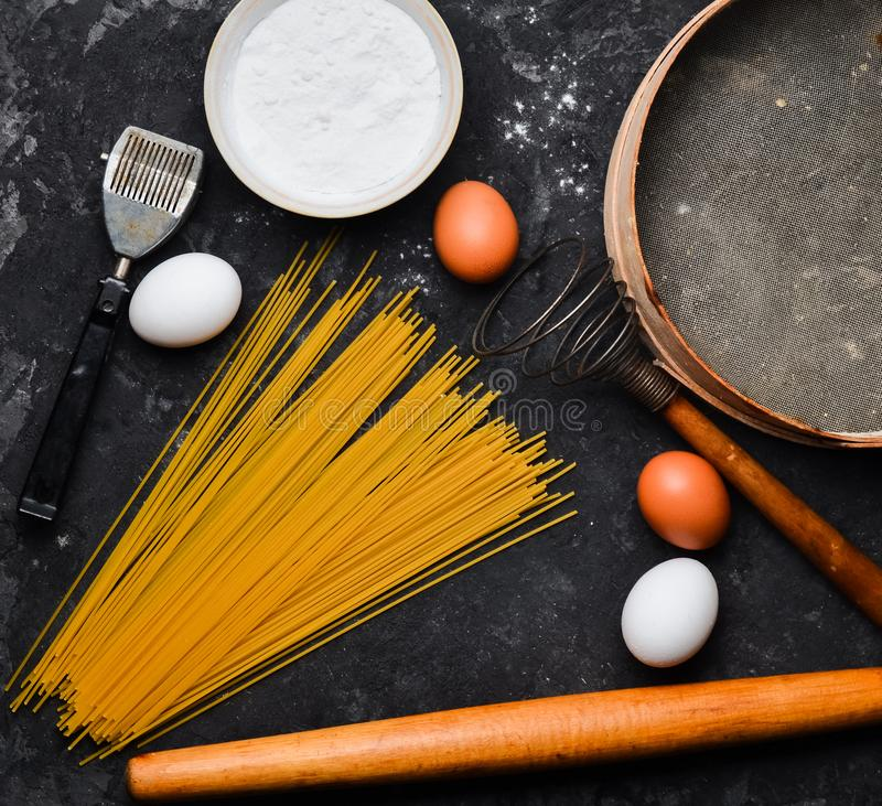 Ingrédients pour des pâtes Le procédé de cuisson Oeufs, farine, outils de cuisine sur une table concrète noire Outils pour la cui photographie stock