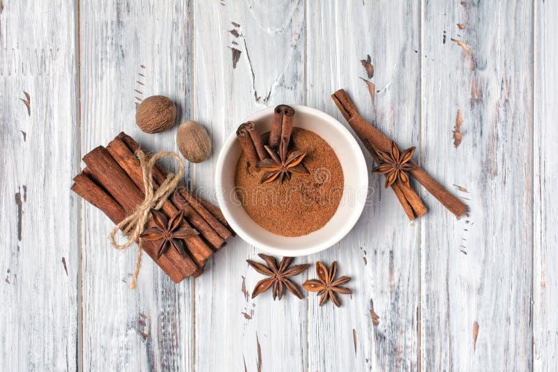 Ingrédients pour des produits de boulangerie - bâtons de cannelle et poudre, étoiles d'anis avec la noix de muscade image stock