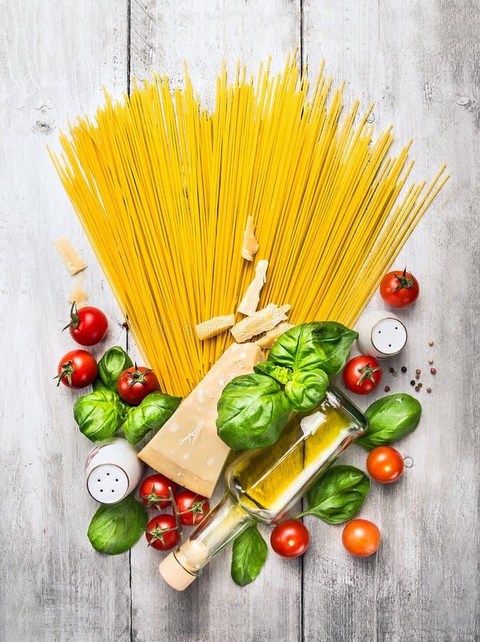Ingrédients pour des spaghetti avec la sauce tomate sur la table en bois blanche photo libre de droits