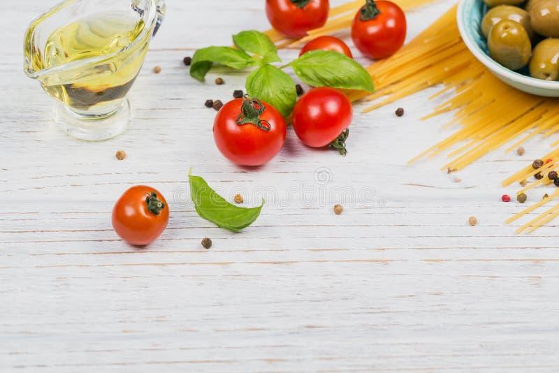 Ingrédients pour des spaghetti de pâtes de préparation - tomate, huile d'olive, épices, herbes, olives vertes, sauce tomate photos stock