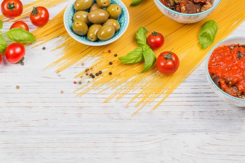 Ingrédients pour des spaghetti de pâtes de préparation - tomate, huile d'olive, épices, herbes, olives vertes, sauce tomate photo libre de droits