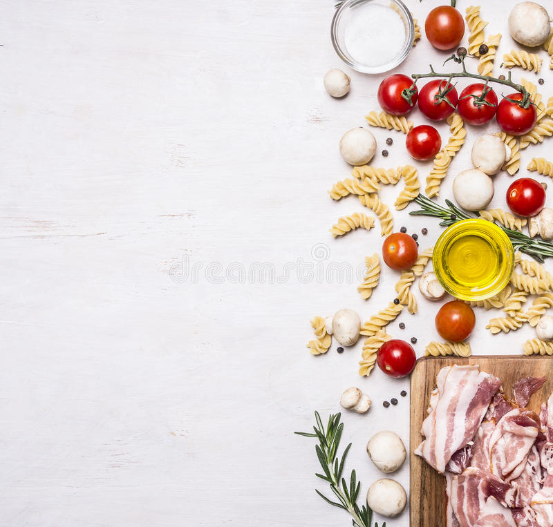 Ingrédients pour faire cuire des pâtes de fusilli avec des légumes de lard, des épices et la frontière d'herbes, texte d'endroit  image stock
