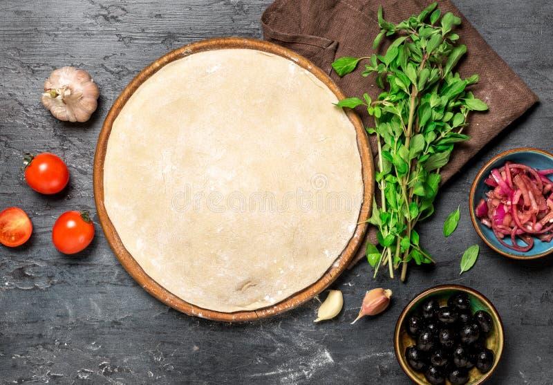 Ingrédients pour faire cuire la pizza végétarienne sur une surface en pierre foncée image stock