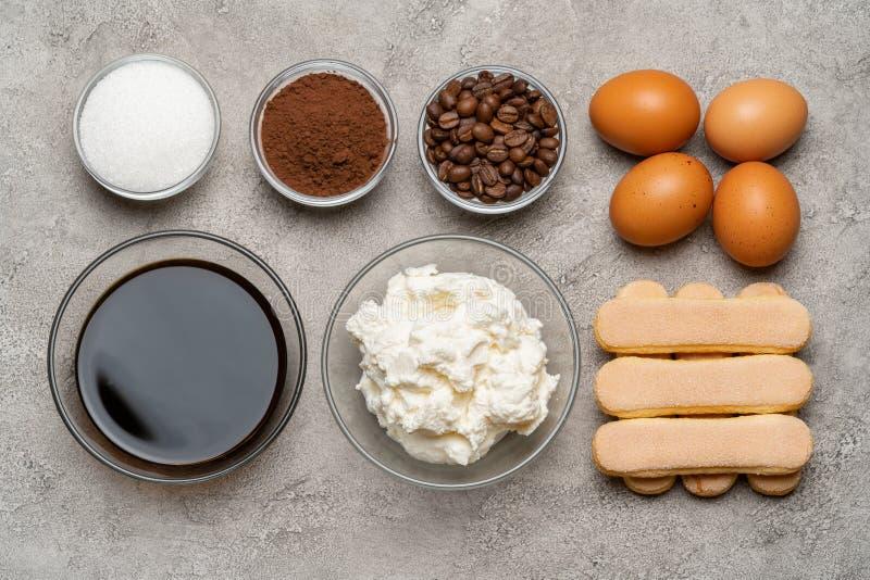 Ingrédients pour faire cuire le tiramisu - biscuits, mascarpone, fromage, sucre, cacao, café et oeuf de biscuit de Savoiardi photos stock