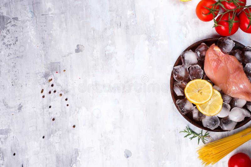 Ingrédients pour faire cuire les pâtes italiennes avec le poulet et les tomates avec la tranche et la glace de citron Protéines m photographie stock