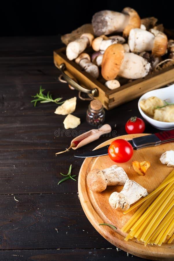 Ingrédients pour faire cuire les pâtes italiennes - spaghetti, tomates, champignons et verts au fond en bois foncé images libres de droits
