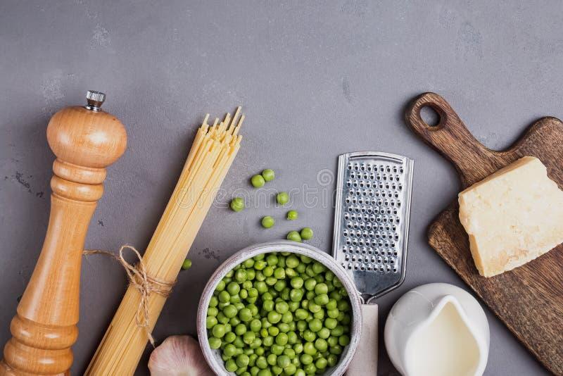 Ingrédients pour faire des spaghetti avec de la crème et des pois sur le fond gris, image libre de droits