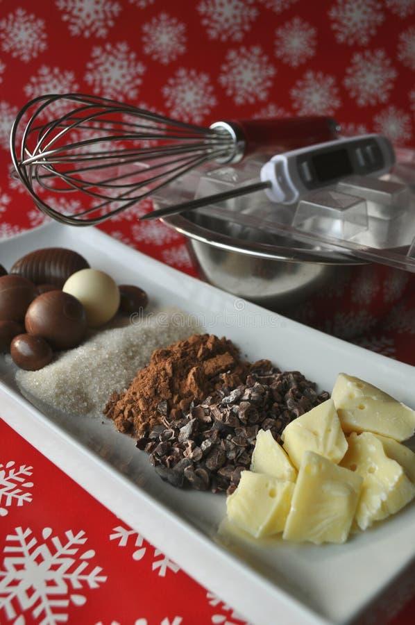 Ingrédients pour faire le chocolat sur un fond rouge d'hiver photo stock