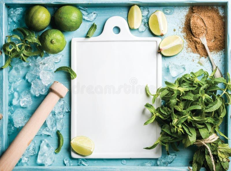 Ingrédients pour faire le cocktail d'été de mojito : glace, feuilles en bon état, sucre roux et chaux ébréchés sur le bleu de tur image stock