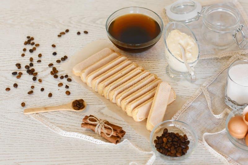 Ingrédients pour faire le tiramisu italien traditionnel de dessert : fromage de mascarpone, savoiardi, café, sur le fond gris-cla image stock